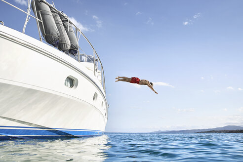 Man jumping off his motor yacht - PDF01084