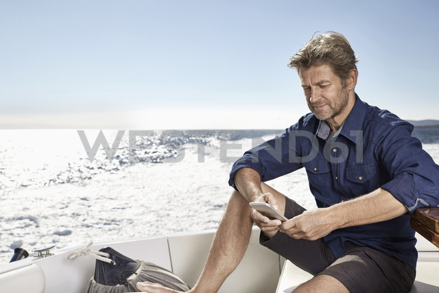 Mature man sitting on his motor yacht looking at cell phone - PDF01096 - Philipp Dimitri/Westend61