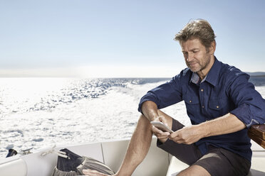 Mature man sitting on his motor yacht looking at cell phone - PDF01096