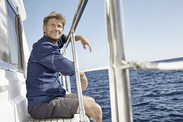 Portrait of content mature man sitting on his motor yacht - PDF01099
