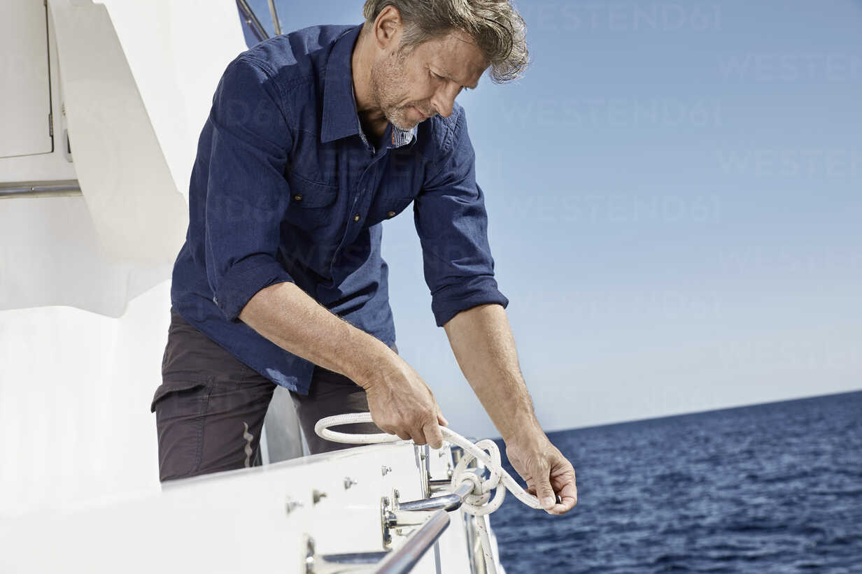 Man on motor yacht tying a knot - PDF01102 - Philipp Dimitri/Westend61