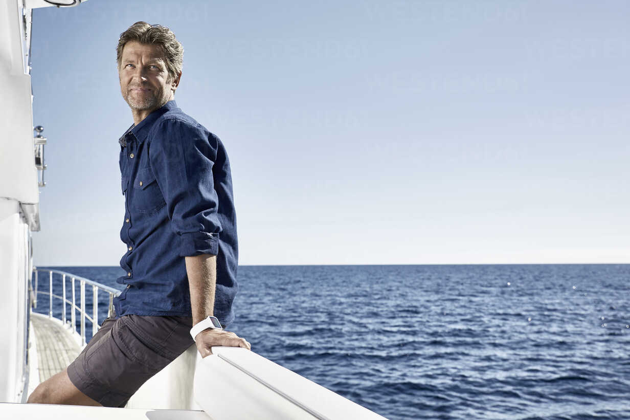Smiling mature man with smartwarch on his motor yacht - PDF01105 - Philipp Dimitri/Westend61