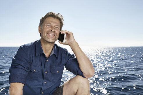 Portrait of smiling mature man on the phone in front of the sea - PDF01108