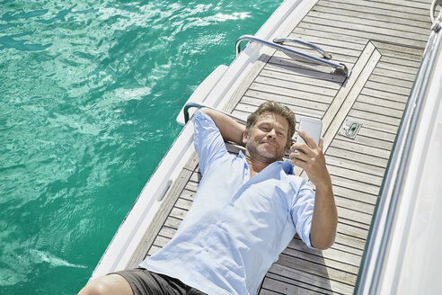 Smiling man lying on deck of his motor yacht checking emails - PDF01117