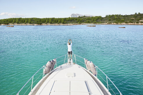 Back view of man standing at bow of his motor yacht taking picture with tablet - PDF01120