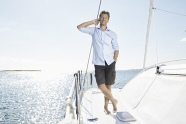Mature man standing on sailing boat - PDF01129
