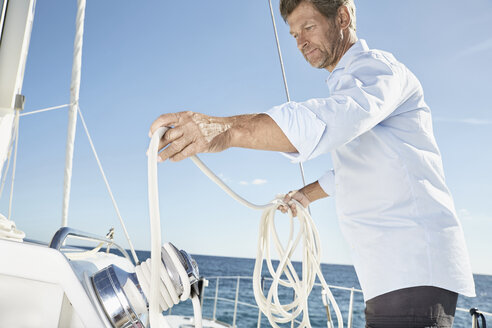 Mature man working with ropes on sailing boat - PDF01135