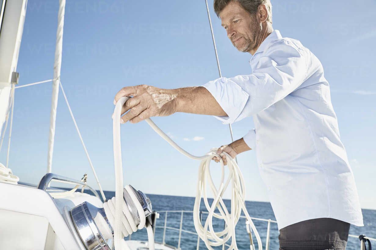 Mature man working with ropes on sailing boat - PDF01135 - Philipp Dimitri/Westend61