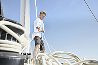 Smiling mature man working with ropes on sailing boat - PDF01138