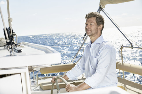 Mature man at helm of his sailing boat - PDF01141