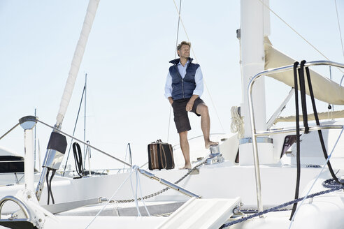 Mature man lying on his sailing boat looking at distance - PDF01144