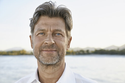 Portrait of smiling mature man with stubble in front of the sea - PDF01147