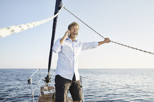 Laughing mature man on the phone on his sailing boat - PDF01153