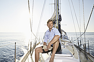 Portrait of smiling mature man with tablet sitting on his sailing boat - PDF01156