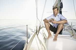 Smiling mature man sitting on his sailing boat using cell phone - PDF01159