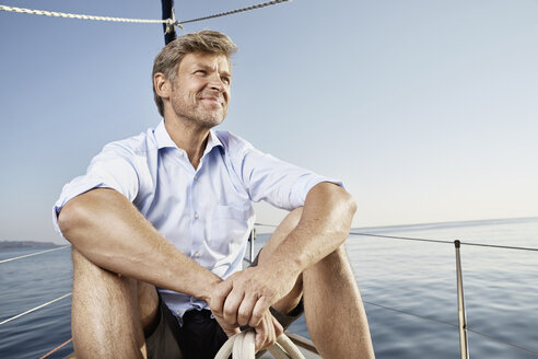 Portrait of smiling mature man sittiing on his sailing boat looking at distance - PDF01171