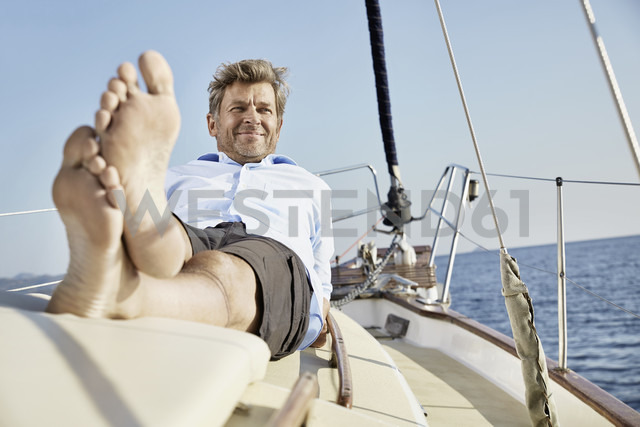 Portrait of smiling mature man lying on deck of his sailing boat - PDF01174 - Philipp Dimitri/Westend61