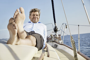 Portrait of smiling mature man lying on deck of his sailing boat - PDF01174