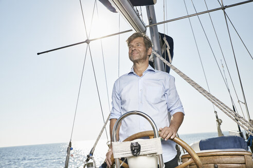 Mature man at helm of his sailing boat - PDF01177