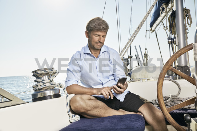 Mature man sitting on deck of his sailing boat using cell phone - PDF01180 - Philipp Dimitri/Westend61
