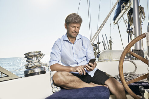 Mature man sitting on deck of his sailing boat using cell phone - PDF01180