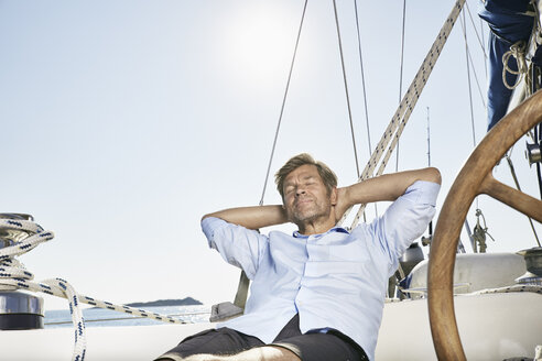 Portrait of smiling mature man relaxing on his sailing boat - PDF01183