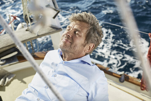 Portrait of smiling mature man lying on deck of his sailing boat - PDF01189