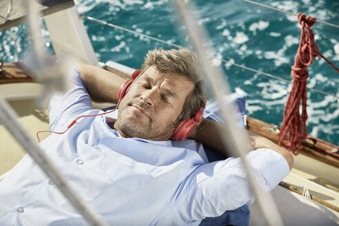 Portrait of mature man listening music with headphones on sailing boat - PDF01192