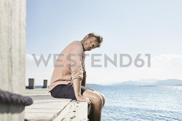 Smiling man sitting on jetty - PDF01198 - Philipp Dimitri/Westend61