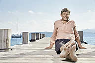 Smiling man sitting on jetty looking at tablet - PDF01201