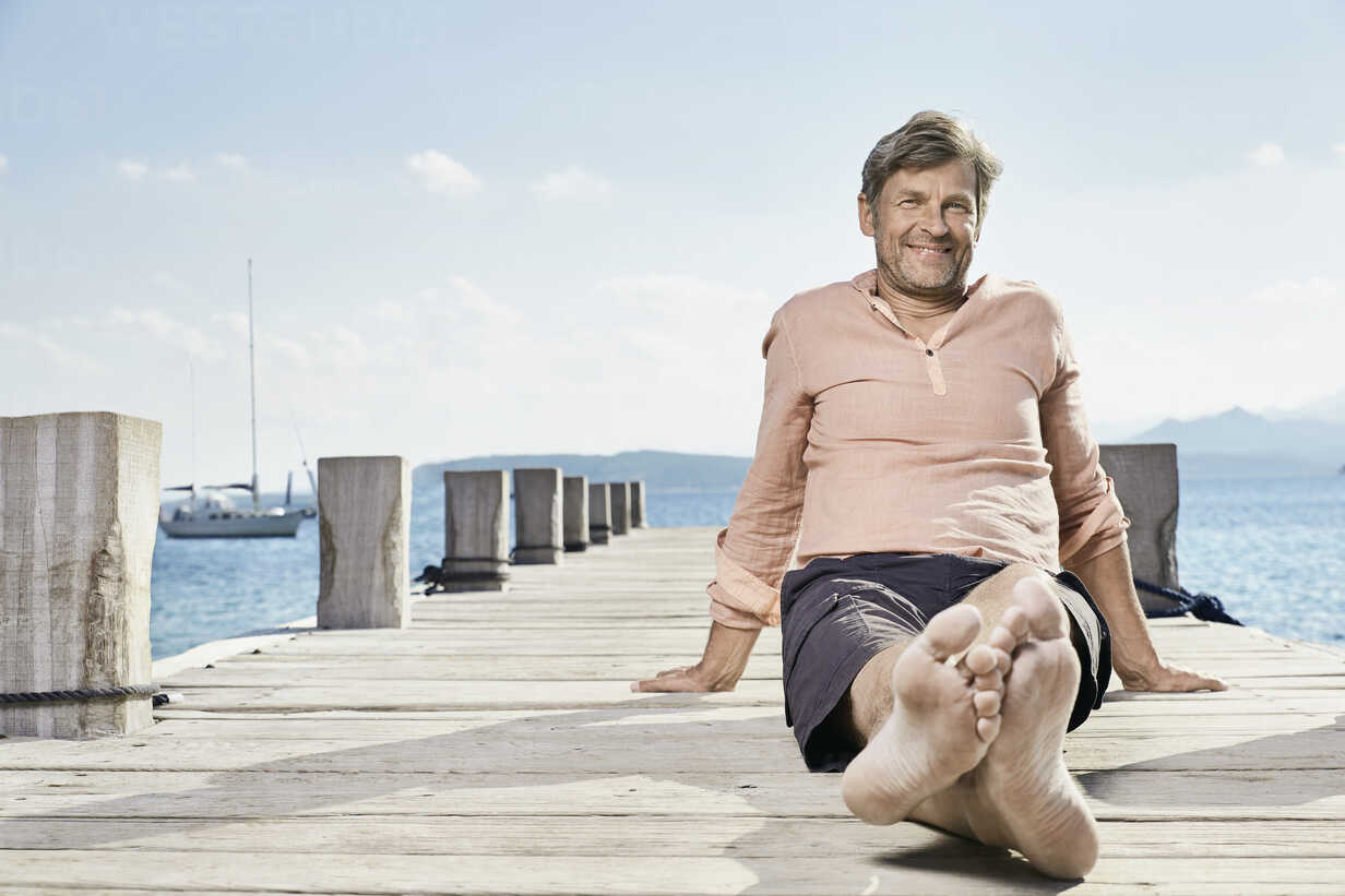 Smiling man sitting on jetty looking at tablet - PDF01201 - Philipp Dimitri/Westend61