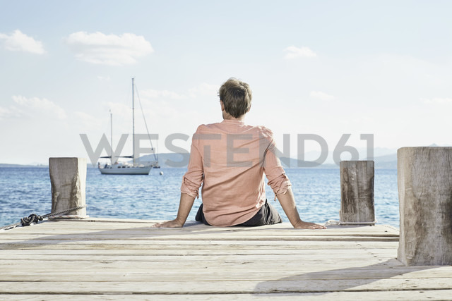 Back view of man sitting on jetty looking at distance - PDF01204 - Philipp Dimitri/Westend61