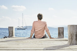 Back view of man sitting on jetty looking at distance - PDF01204