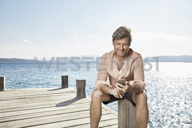 Smiling man sitting on jetty looking at cell phone - PDF01207 - Philipp Dimitri/Westend61