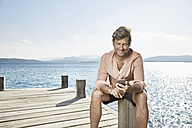 Smiling man sitting on jetty looking at cell phone - PDF01207
