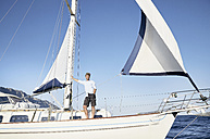Mature man standing on his sailing boat - PDF01216