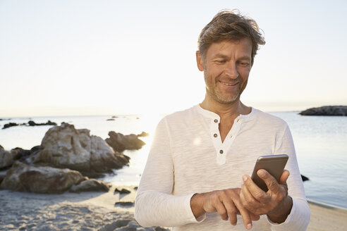Portrait of smiling man using cell phone on the beach - PDF01219