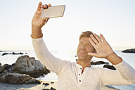 Portrait of smiling man taking selfie on the beach with cell phone - PDF01222