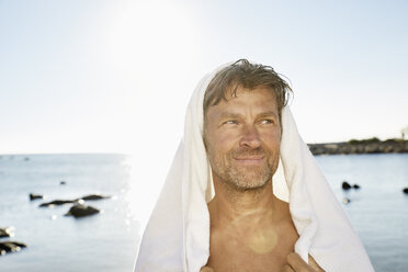 Portrait of smiling man with towel in front of the sea - PDF01225
