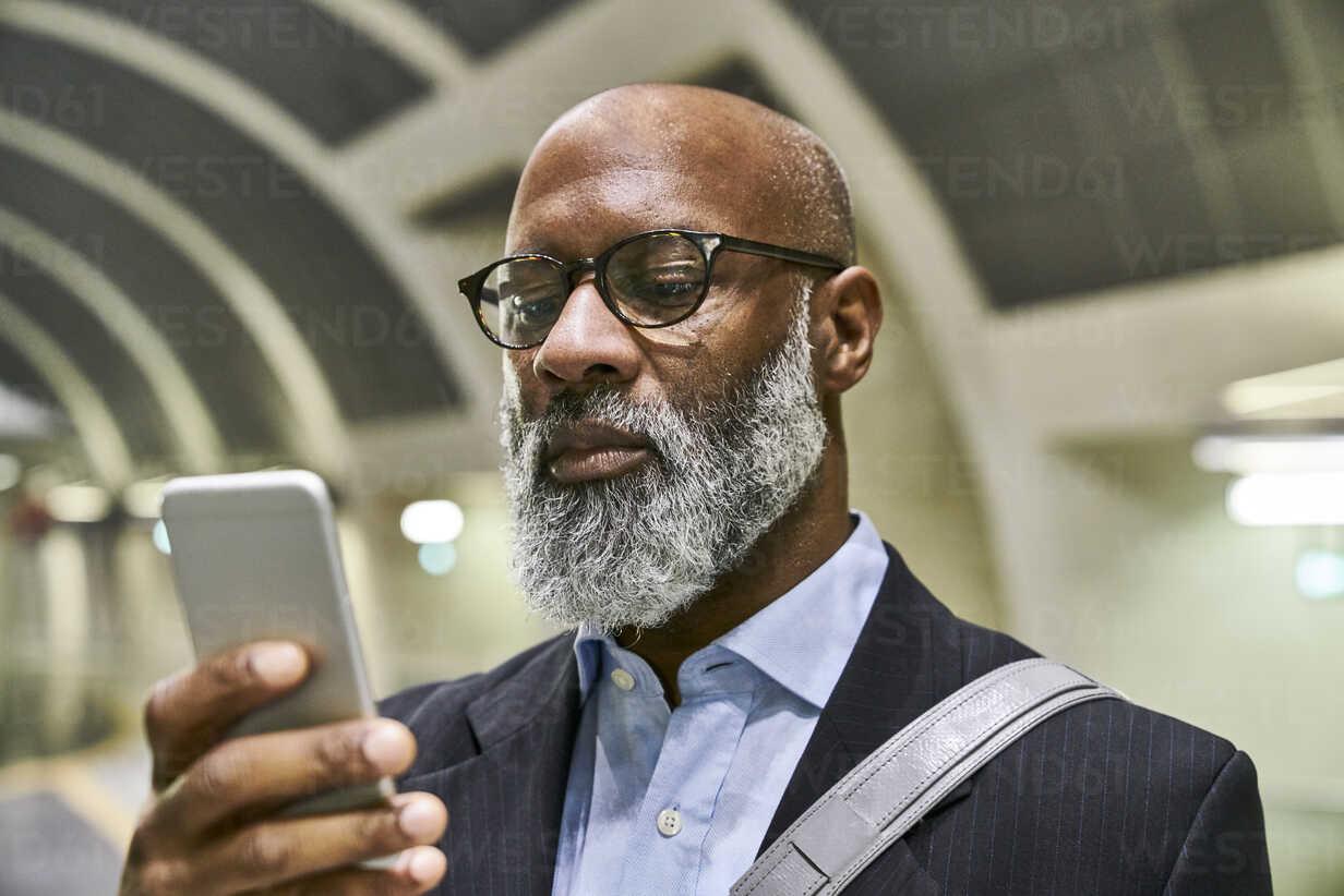 Businessman with smartphone reading messages on escalator - FMKF03787 - Jo Kirchherr/Westend61