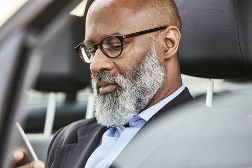 Businessman sitting in car using smartphone - FMKF03802