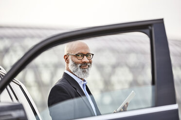 Businessman with digital tablet standing by car - FMKF03805