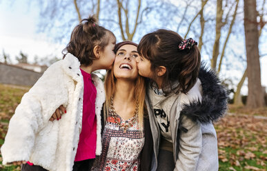 Happy mother kissed by her little daughters - MGOF03177