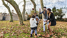 Family playing with autumn leaves in a park - MGOF03180