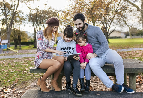 Family sitting on bench in autumnal park looking at tablet - MGOF03183