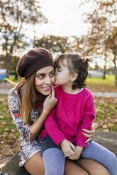 Little girl kissing her mother in autumnal park - MGOF03189