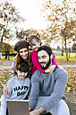 Family with tablet in autumnal park - MGOF03192