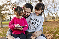 Father with his little daughters looking at tablet in autumnal park - MGOF03195