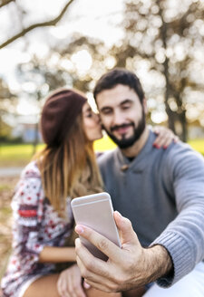 Couple taking selfie with smartphone in autumnal park, close-up - MGOF03198
