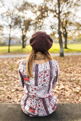 Back view of young woman wearing beret sitting on bench in autumn - MGOF03201